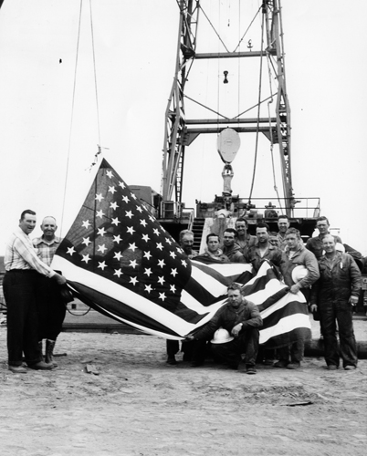 A crew from Rowan Drilling Company and General Petroleum Corporation at an Alaska rig hoist a new flag the day Alaska became the 49th star, July 4, 1959. ExxonMobil Historical Collection. di_06172