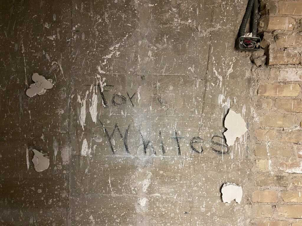 """Detail of handwritten sign that reads """"For Whites"""" on a previously hidden interior wall of Battle Hall, 2021."""